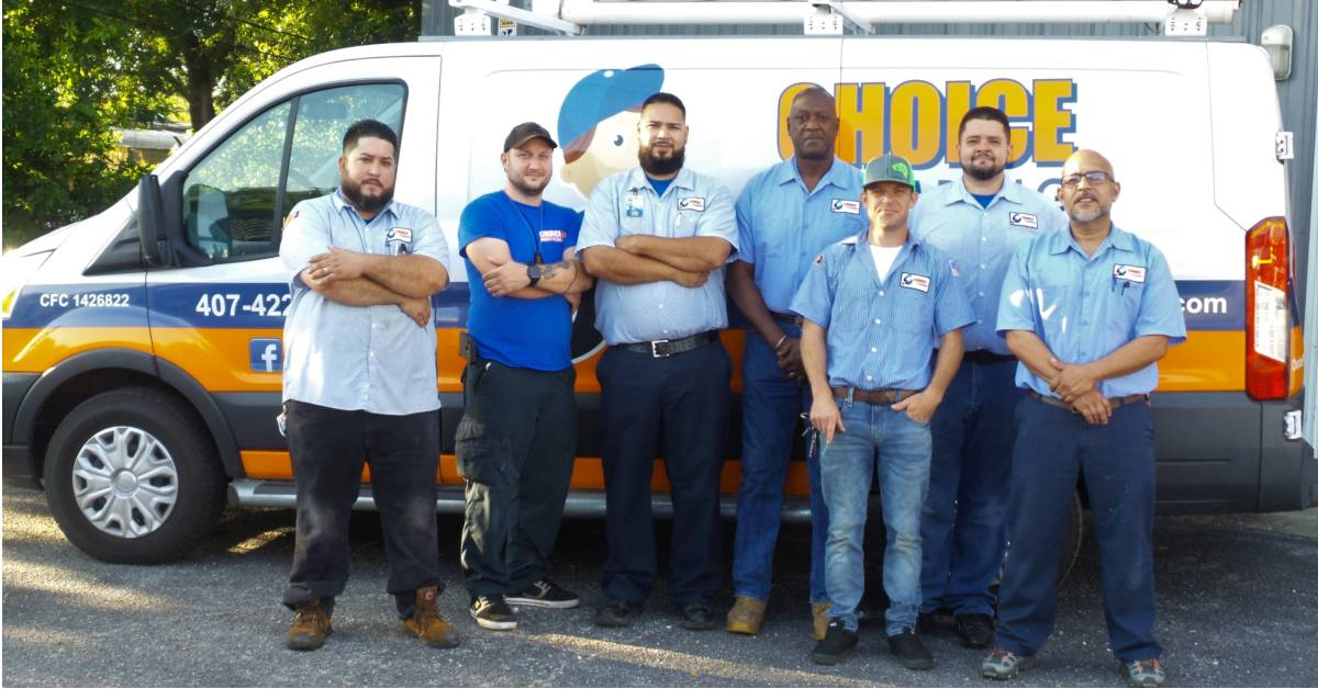 View of seven Orlando plumbers from Choice Plumbing standing in front of their company van.